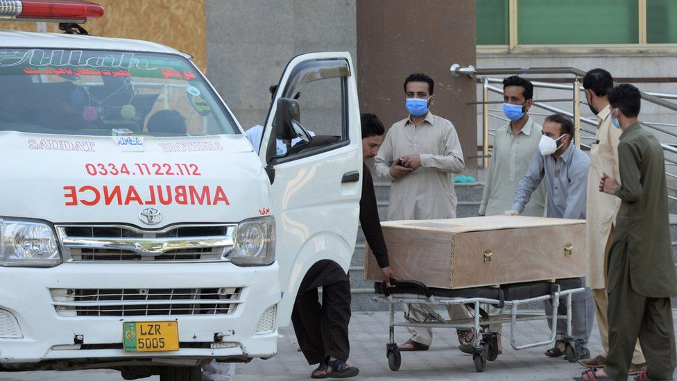 A body of a Covid-19 victim is moved to an ambulance in Rawalpindi, Pakistan