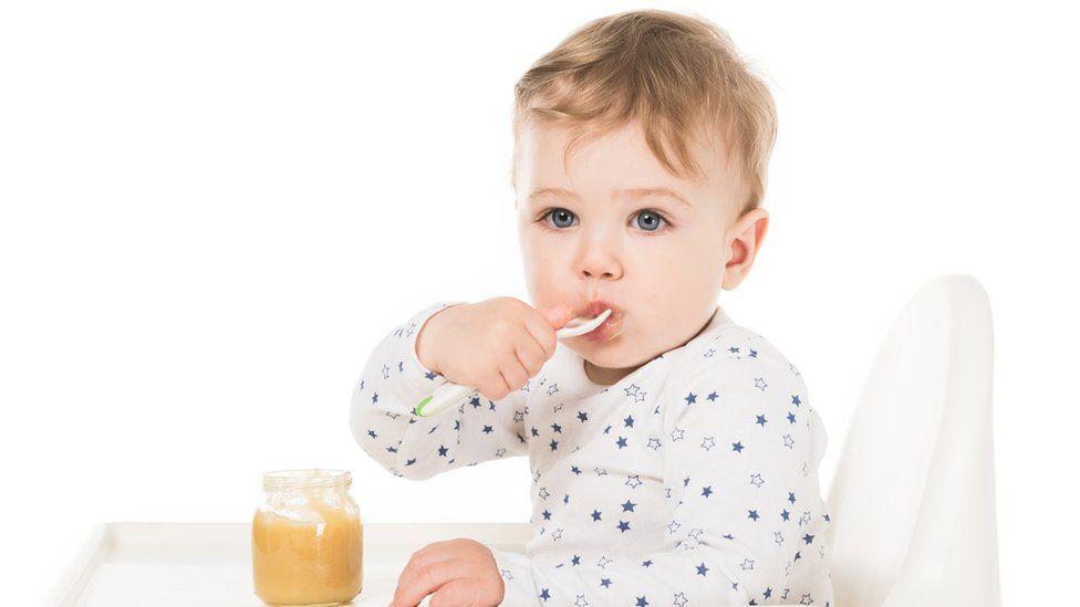 Toddler eating a jar of baby food
