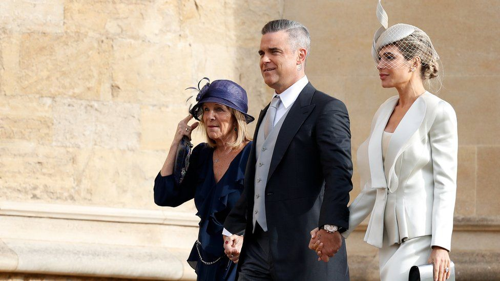 British singer-songwriter Robbie Williams arrives with his wife US actress Ayda Field and her mother Gwen to attend the wedding