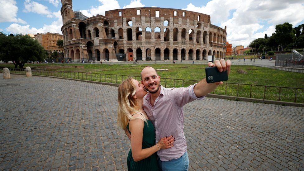 A couple take a picture outside the Colosseum