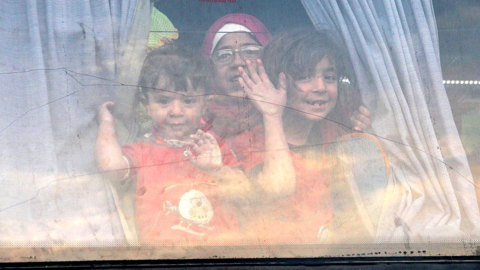 Children smile and wave as they are evacuated from the rebel-held Syrian town of Zabadani on 21 April 2016