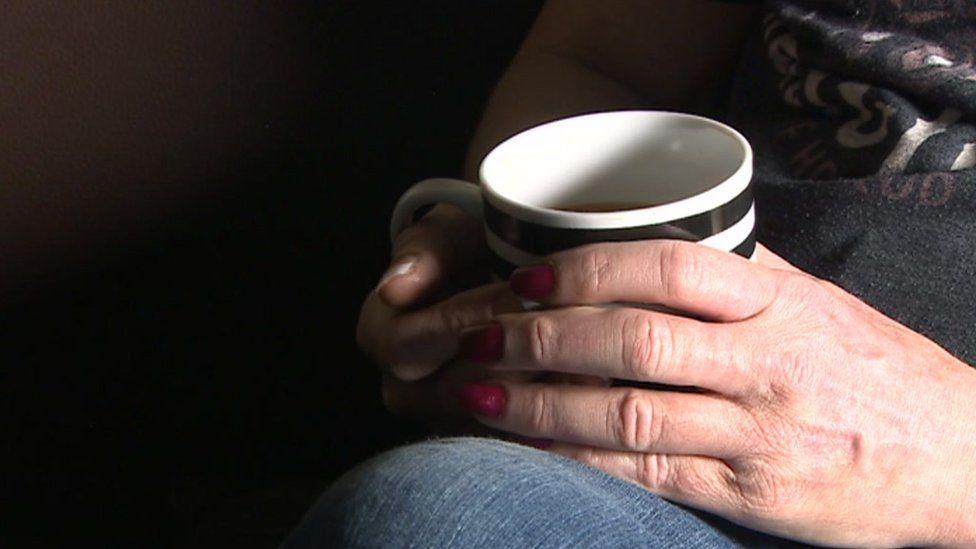 Sarah holding a cup of tea