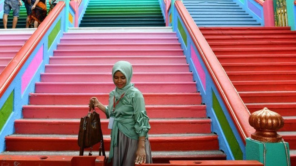 A girl poses in front of the staircase leading to the Batu Caves temple complex in Kuala Lumpur