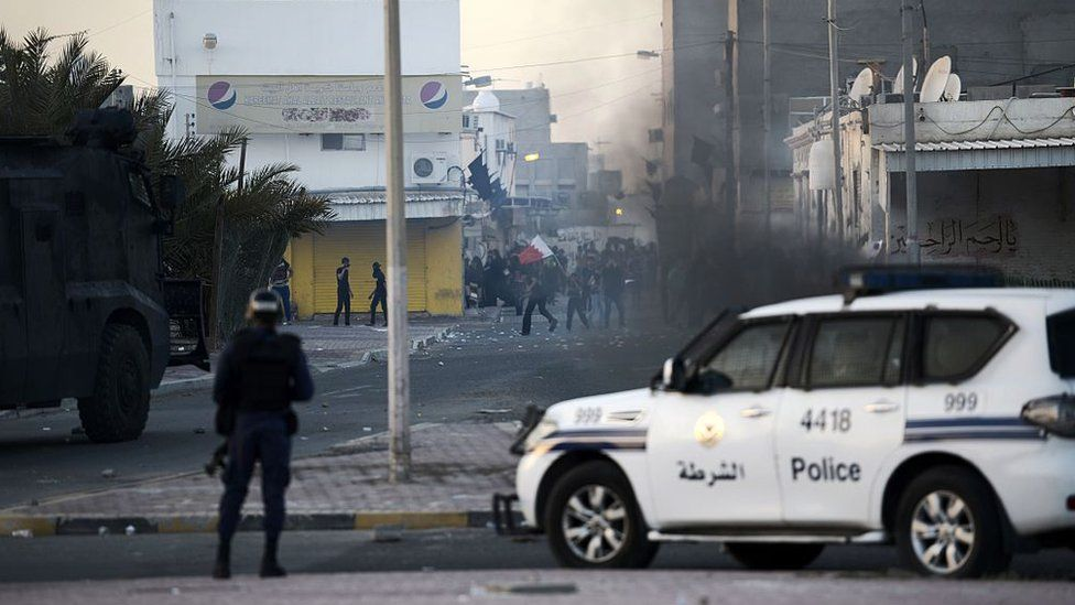 Bahraini protesters throw stones towards riot police during clashes in the village of Shahrakkan, south of Manama, on 5 April 2016