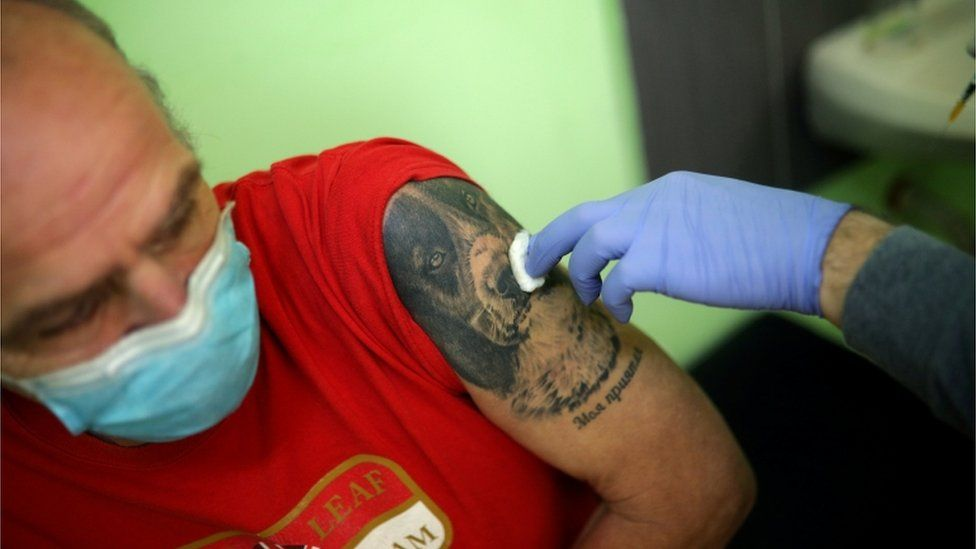 A man sits after receiving a dose of AstraZeneca's coronavirus disease (COVID-19) vaccine administered by a medical personnel from a mobile unit in the village of Ogden, Bulgaria, 25 February 2021.
