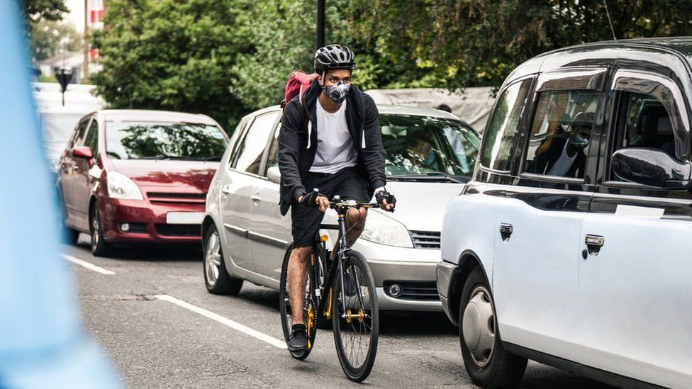 picture of man cycling through road traffic