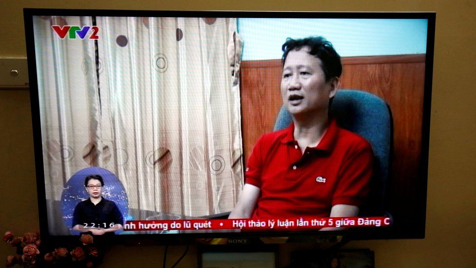 Thanh is seen seated in a chair in a TV news report. The photo is of a TV showing the broadcast.
