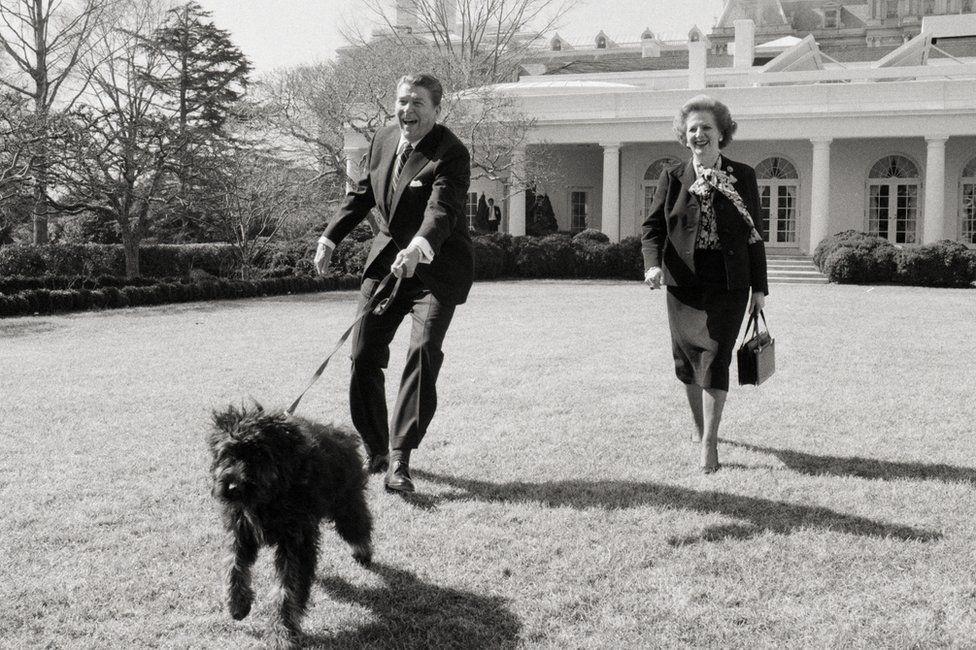 President Reagan and Prime Minister Margaret Thatcher walk a dog together