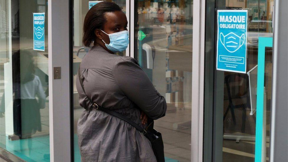 A woman wearing a mask in Antwerp enters a shop
