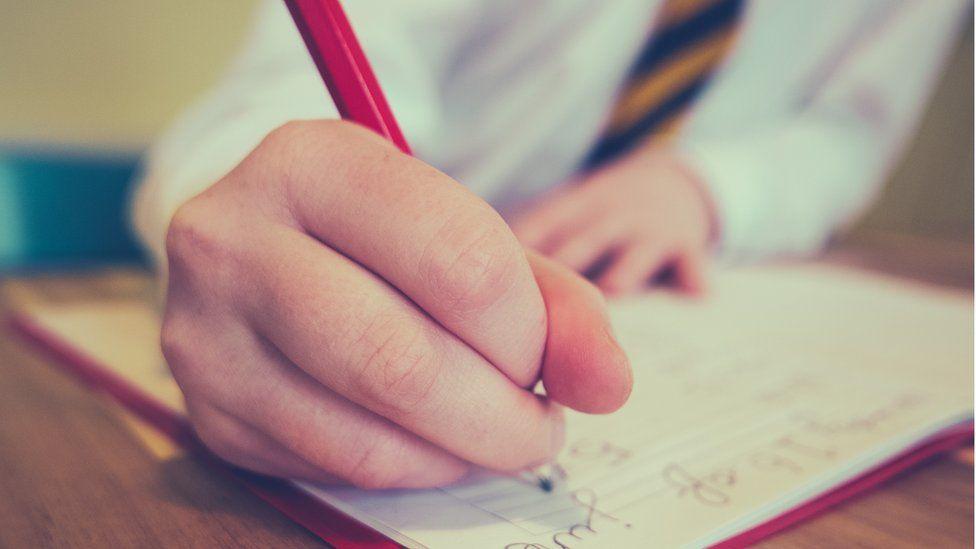 child's hand writing homework