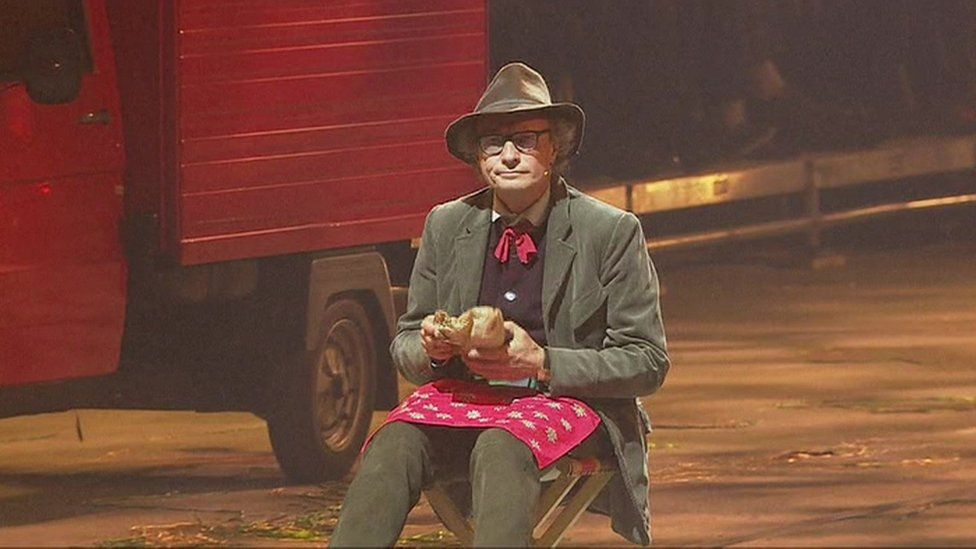 Actor sitting down eating a sandwich as milk floats drive by during opening ceremony of Gotthard rail tunnel - 1 June 2016