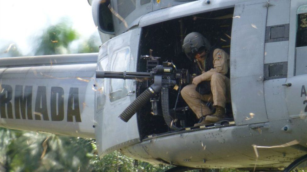 A soldier looks out a helicopter gunship on patrol in Putumayo province in the Colombian Amazon