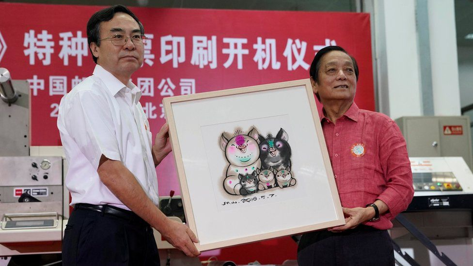 Designer Han Meilin (R) poses for pictures as he presents his design manuscript for a Year of the Pig stamp that shows a five-member pig family to Liu Aili, president of China Post, at a ceremony in Beijing, China 6 August 2018