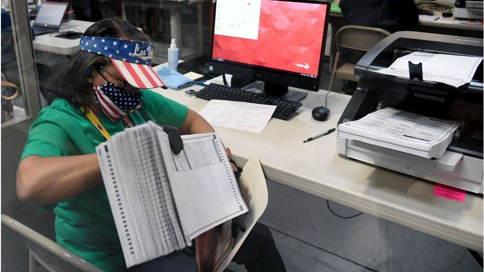 An election worker in Nevada counts mail-in ballots