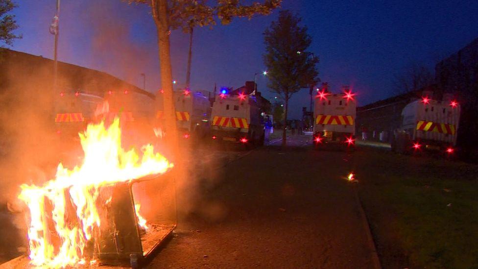 Police Land Rovers parked near a burning bin in Belfast