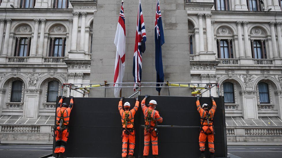 Workers erect a protective barrier around the Cenotaph in anticipation of protests tomorrow