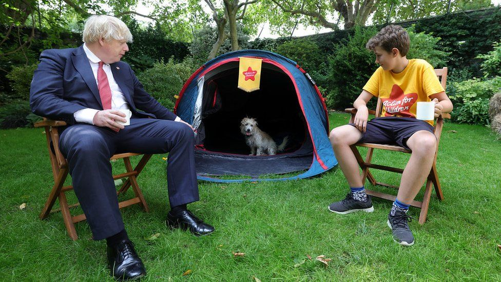 Boris Johnson and Max Woosey look into tent as Dilyn the dog looks back out