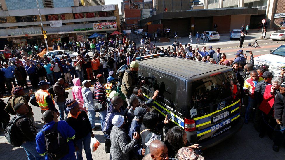 Journalists crowd around a van believed to be carrying Olympic and Paralympic track star Oscar Pistorius after his sentencing in Pretoria, South Africa on 6 July