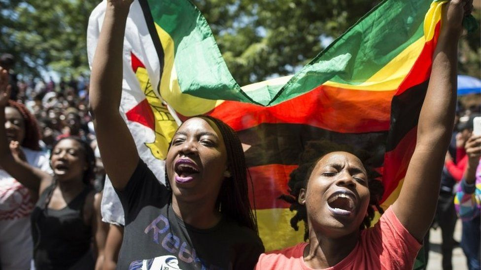 Women holding a flag of Zimbabwe take part in a demonstration of University of Zimbabwe's students, on November 20, 2017 in Harare