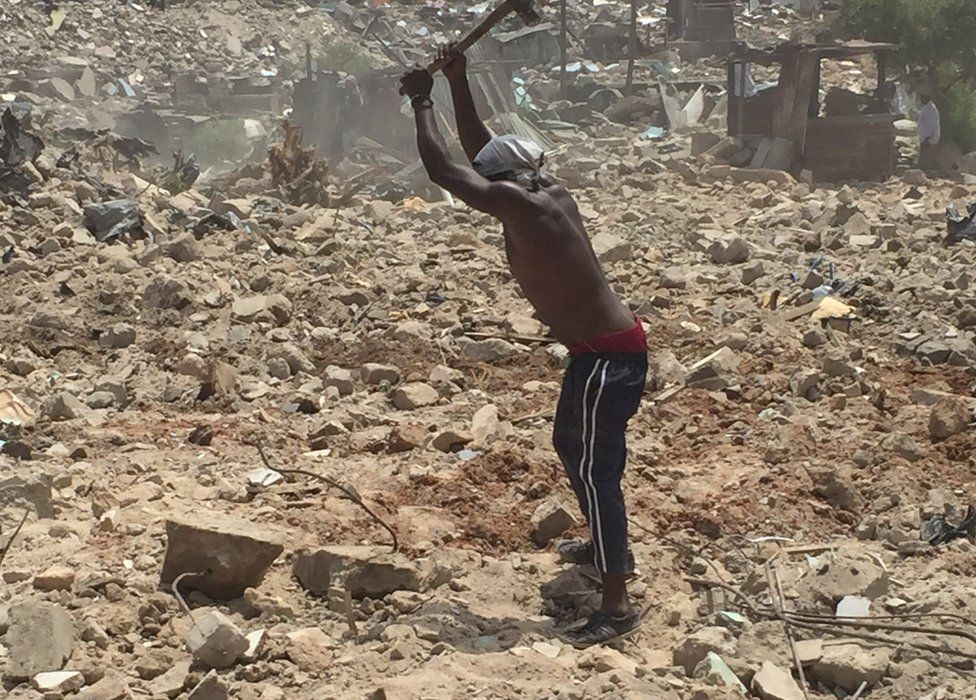 A man breaking rubble at the site of demolitions in Dar es Salaam, Tanzania