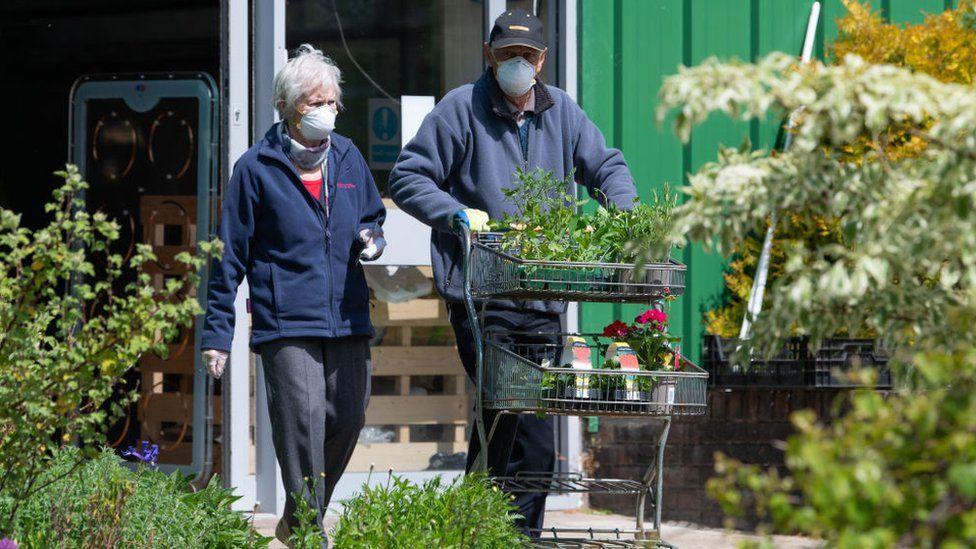 Couple in masks at garden centre