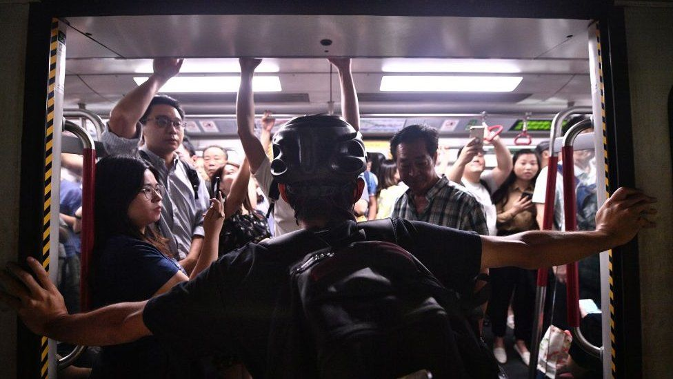 A protester blocks the MTR underground train from closing