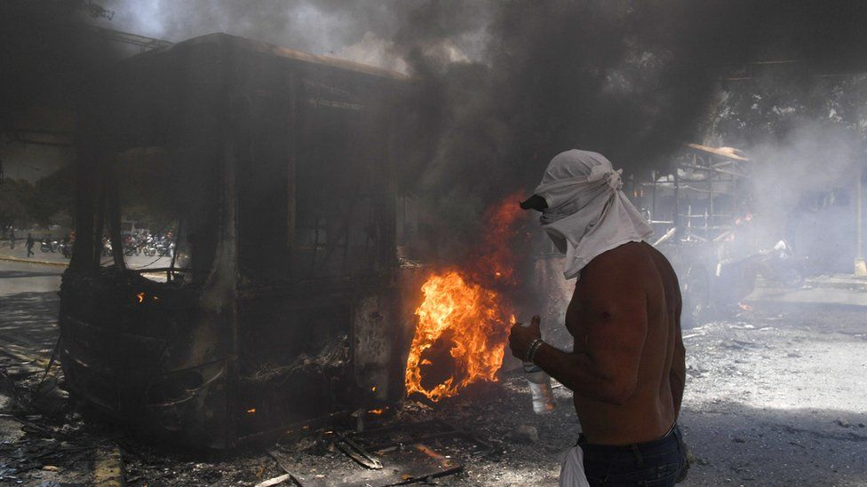 An opposition demonstrator is seen next to a government bus set on fire during clashes with soldiers loyal to Venezuelan President Nicolas Maduro