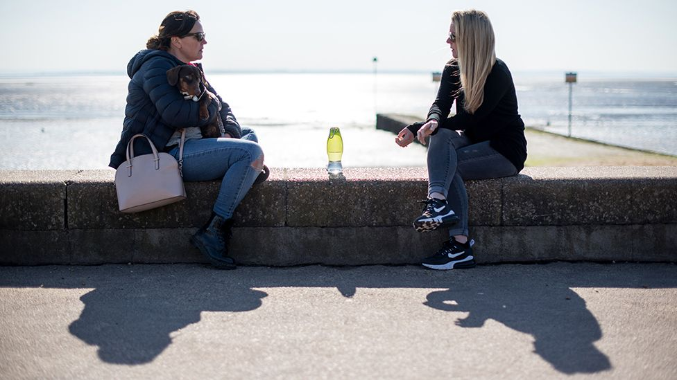 Two women talking on the sea front, Southend-on-Sea, 9 March