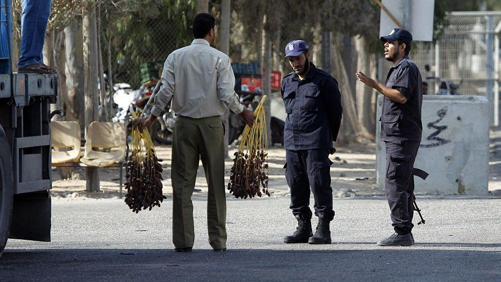 Gaza security personnel inspect goods which have been brought across from Israel