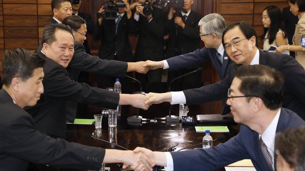 South Korean Unification Minister Cho Myoung-Gyon (2nd R) shakes hands with his North Korean counterpart Ri Son Gwon (2nd L) after their meeting on August 13, 2018 in Panmunjom, North Korea