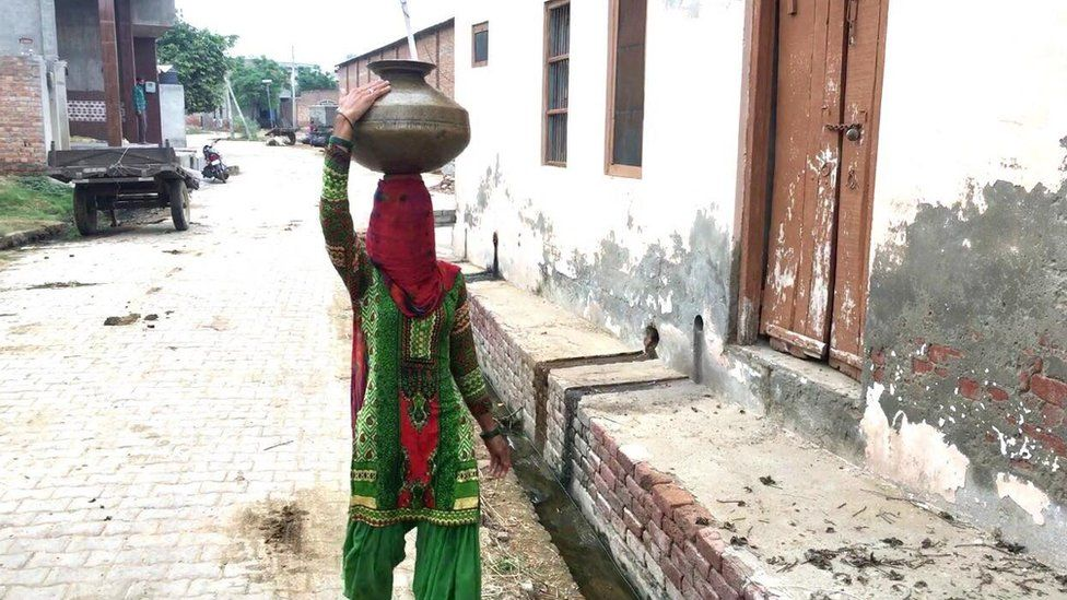 A woman carrying a pot of water in Dharondi village.