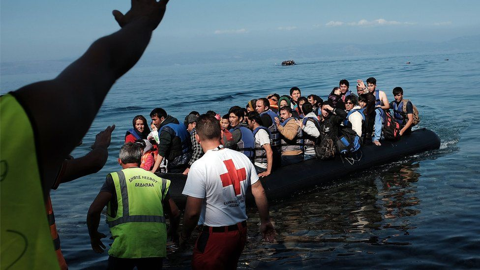 A group of migrants land on a beach on the Greek island of Lesbos after crossing from Turkey (19 October 2015)