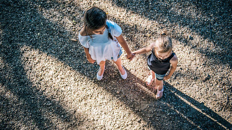 two girls hold hands