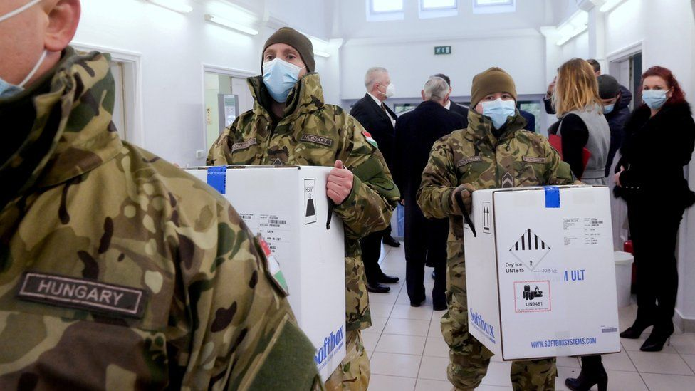Hungarian soldiers carry the first shipment of Pfizer-BioNTech vaccines