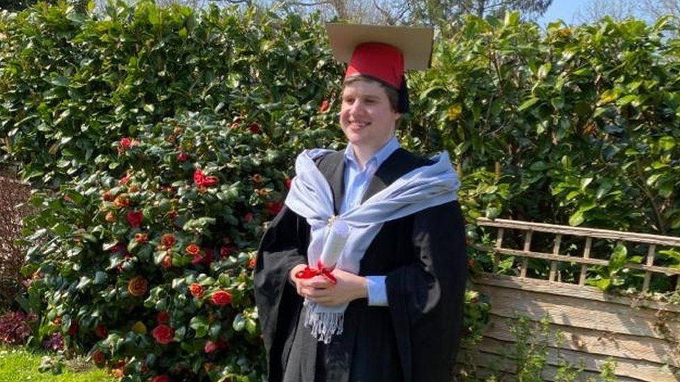 David Harvey in graduation gown and makeshift hat.