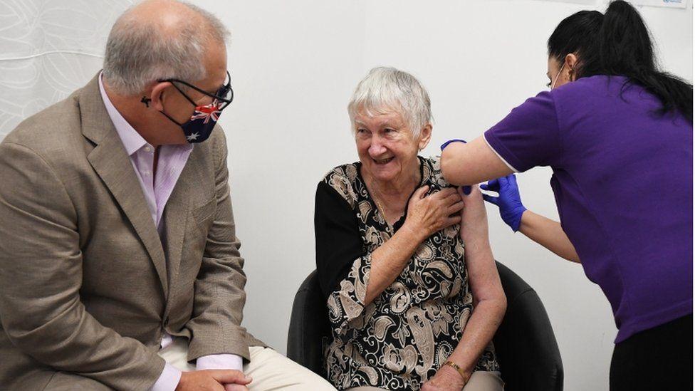 Woman receiving vaccine jab sitting next to Scott Morrison