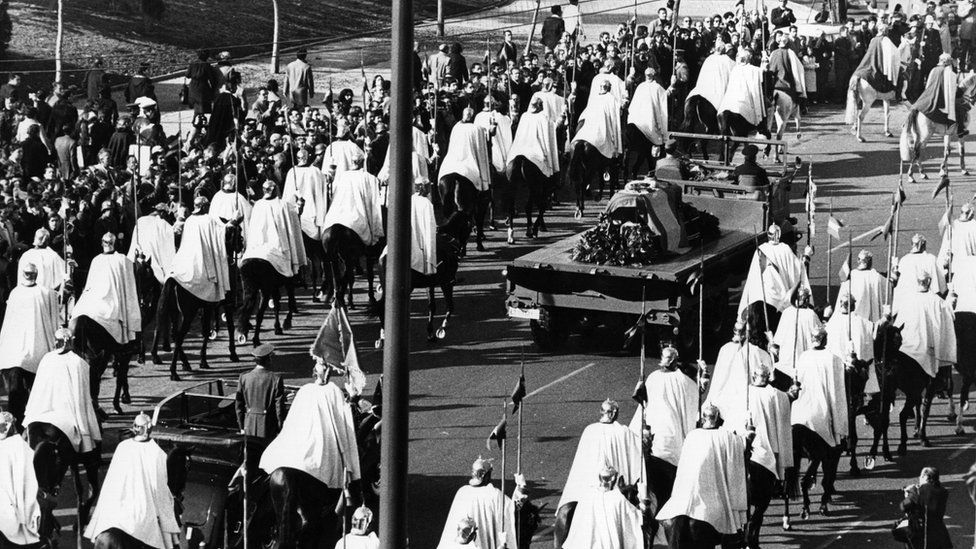 The funeral procession for Franco in 1975 towards the Valley of the Fallen. His flag-draped coffin is flanked by men wearing white cloaks on horseback