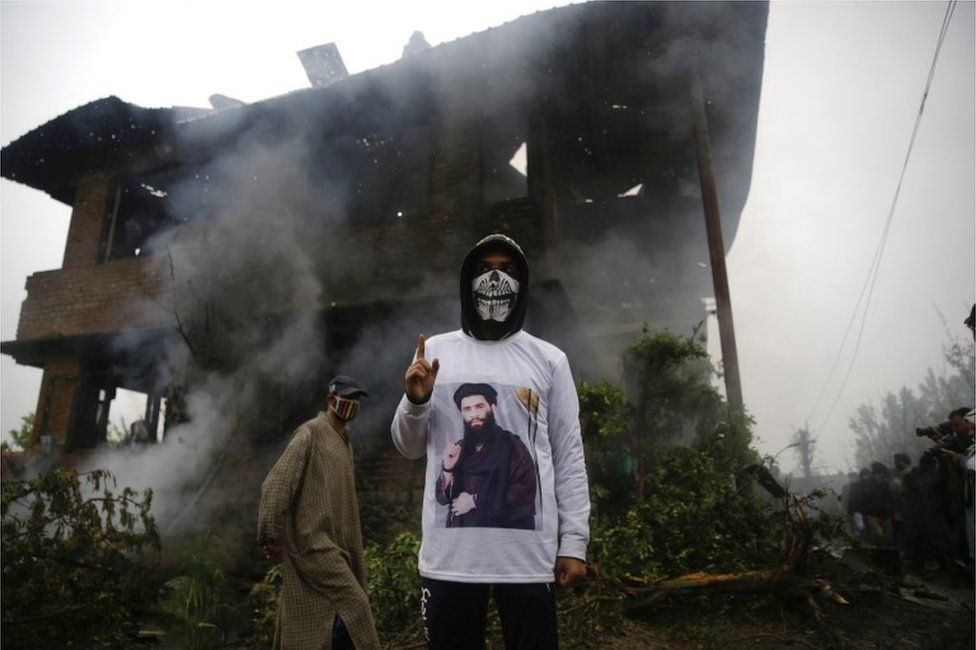 A Kashmiri youth wearing a shirt depicting a picture of militant commander Zakir Musa, as he stands inside of a damaged house where Musa was killed at Dadsara village in Tral, south of Srinagar, the summer capital of Indian Kashmir, 24 May 2019.