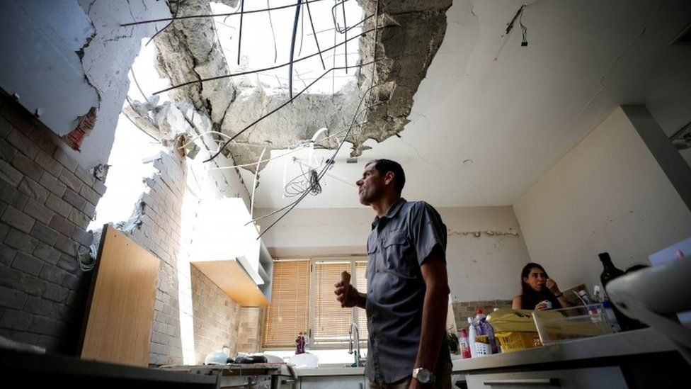Adi Vaizel, looks at the damage caused to the kitchen of his house after it was hit by a rocket launched from the Gaza Strip