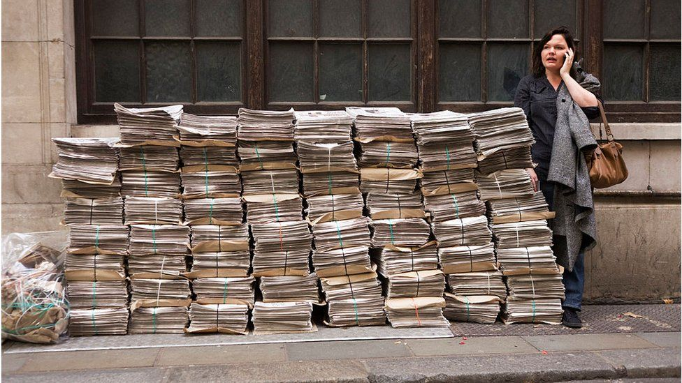 Woman standing next to pile of newspapers