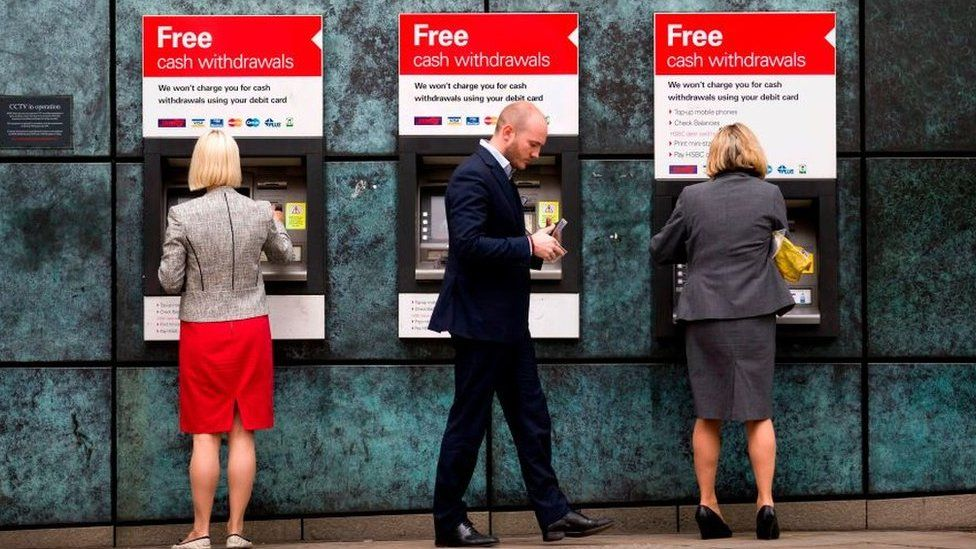Customers use ATM cashpoints outside a HSBC bank branch in London