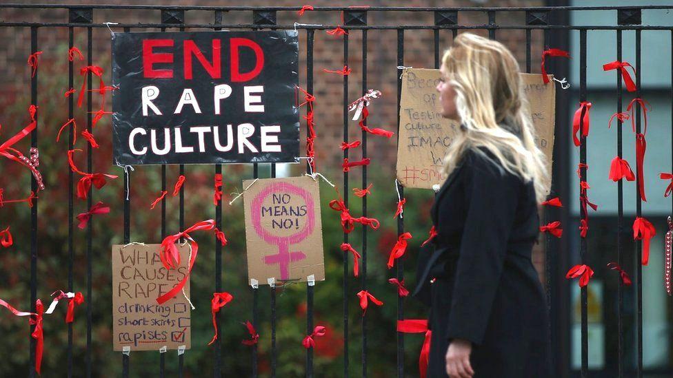 A woman walks past a placard saying 'End Rape Culture'
