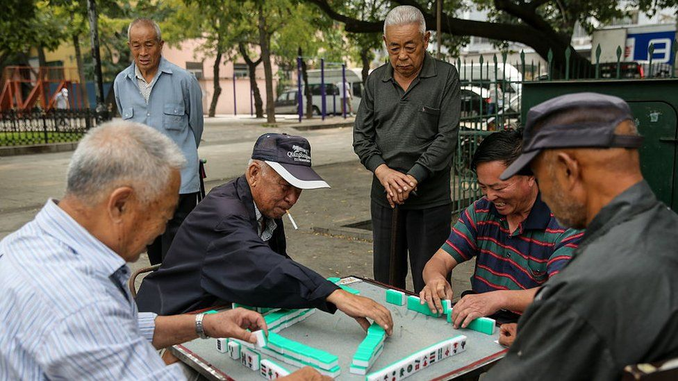 Men play mah-jong in a street