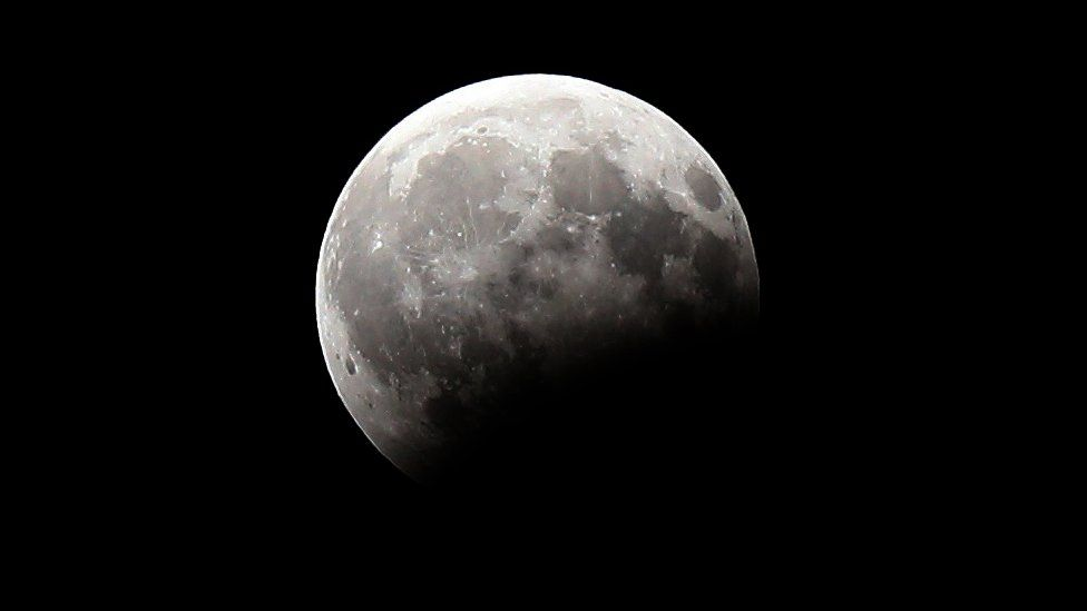 A picture shows the moon during a partial lunar eclipse as seen from Kuwait City on August 7, 2017.