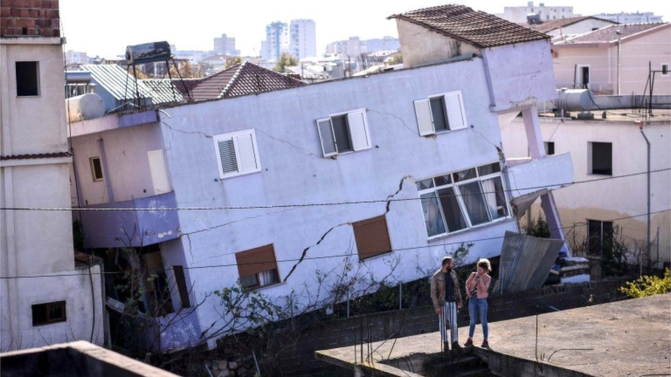 People stand in front of a collapsed building in the town of Durres, western Albania 27 November 2019