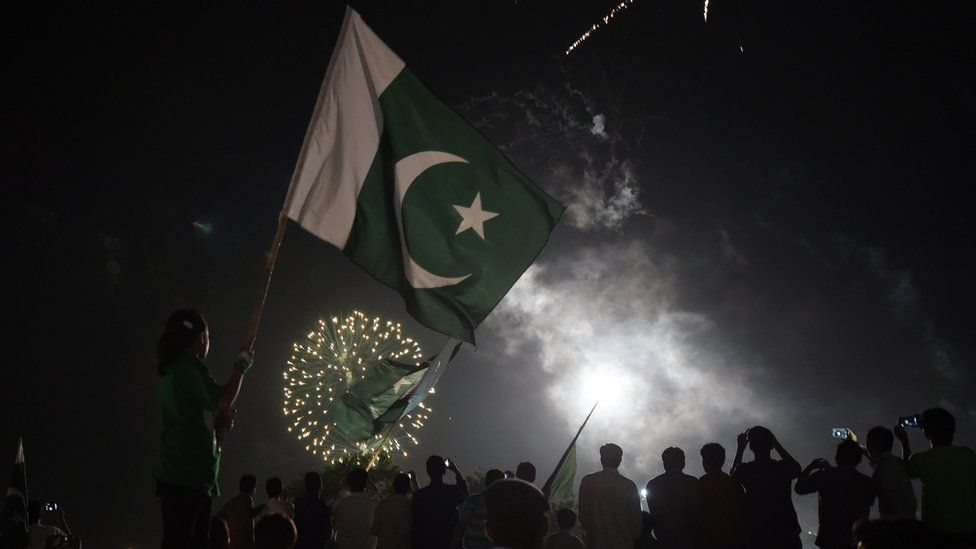 Pakistani residents carry national flags as they watch fireworks in Islamabad on 14 August 2017 to mark Independence Day.