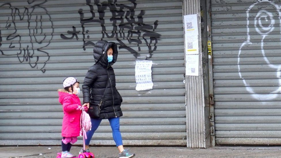 people in masks walk past closed stores