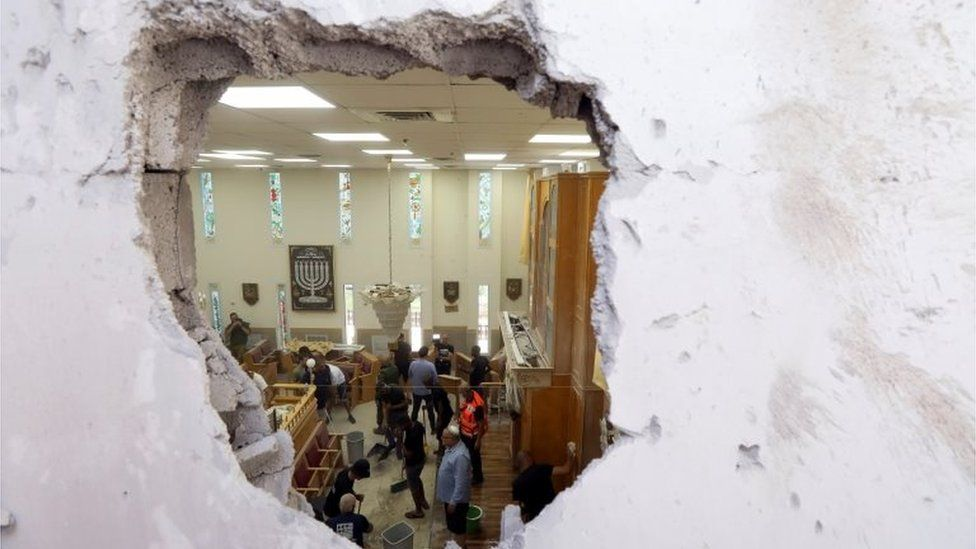 People clean inside a synagogue damaged by a rocket, as Israeli-Palestinian cross-border violence continues, in Ashkelon, southern Israel May 16, 2021