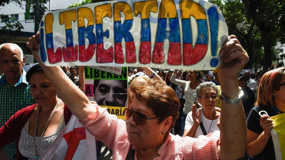 """A demonstrator holds a sign reading """"Freedom"""", during a protest against the government of President Nicolas Maduro, called by opposition leader and self-proclaimed """"acting president"""" Juan Guaido on 30 January"""