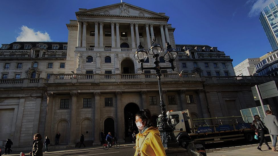 People in masks pass the Bank of England